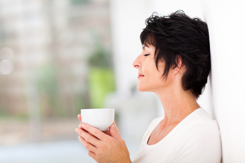 beautiful mature woman enjoying a cup of coffee at home